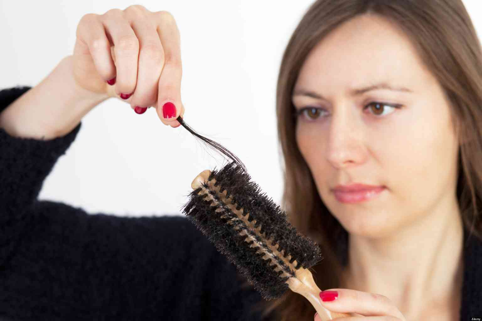 Dark-haired woman being sad, because of having problems with hair loss